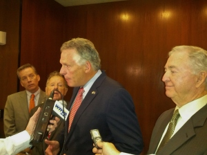 Governor McAuliffe speaks to reporters as budget committee members look on.