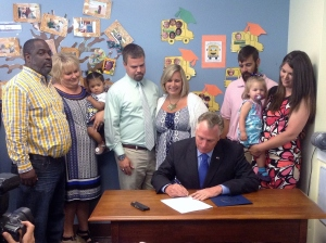 Elly Lafkin (right) and other parents watch as Gov.  McAuliffe signs the bill.