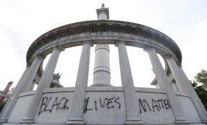 "This June 25, 2015, the words ""Black Lives Matter"" spray painted on a monument to former Confederate President Jefferson Davis in Richmond, Va. Confederate monuments in a half-dozen places this week have been defaced _ a telling sign of the racial tension that permeates post-Ferguson America. AP Photo/Steve Helber,"