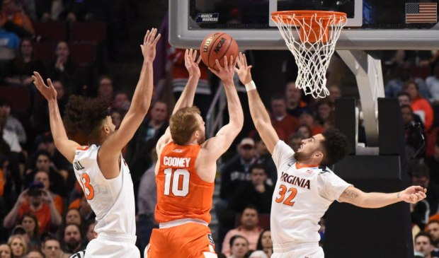 Mar 27, 2016; Chicago, IL, USA; Syracuse Orange guard Trevor Cooney (10) shoots between Virginia Cavaliers guard London Perrantes (32) and forward Anthony Gill (13) during the first half in the championship game of the midwest regional of the NCAA Tournament at United Center. Credit: David Banks-USA TODAY Sports
